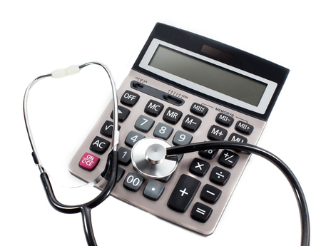 surgery expenses: Medical stethoscope and calculator on a white background. The symbol of paid medical services.