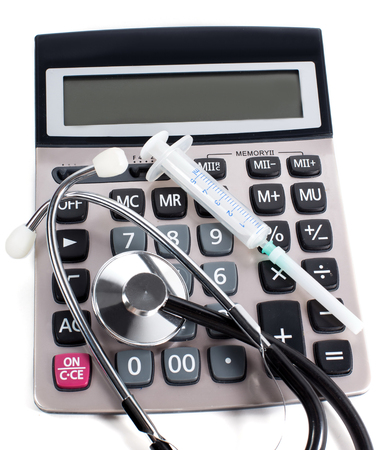 afford: Medical stethoscope and calculator on a white background. The symbol of paid medical services.