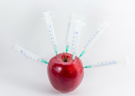Apple in a medical syringe on a gray background. Introduction to fruit chemicals, nitrates.