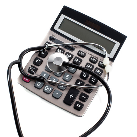 surgery costs: Medical stethoscope and calculator on a white background. The symbol of paid medical services.