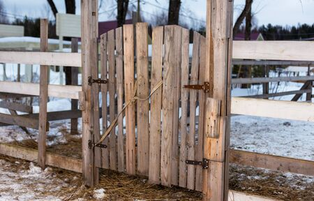 The wooden gate in the fence.