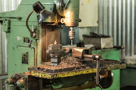 Drilling machine in operation, revolves the spindle, the machine studded with steel shavings. A few finished parts in the frame Reklamní fotografie