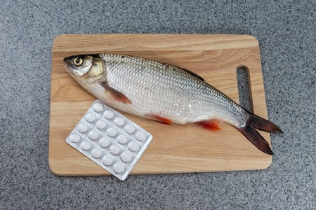 unnatural: Raw fish, not cooked. Fish on a cutting Board, lay next to the pills. Symbolizes allergic to fish or the contamination of food, unnatural food. Or the risk of infection when consuming fish.