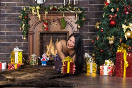 Woman, girl under the tree, under the Christmas tree, spruce. Next to the fireplace. Gifts.