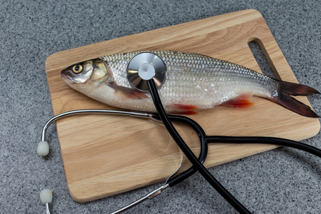 Raw fish, not cooked. Fish on a cutting Board, lying next to a stethoscope. The doctors recommend. Symbolizes allergic to fish or artificiality of food or the risk of infection when consuming fish. The need for medical care.
