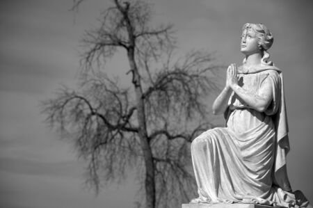 Black and White image of praying statue in Riverside Cemetery. Banco de Imagens