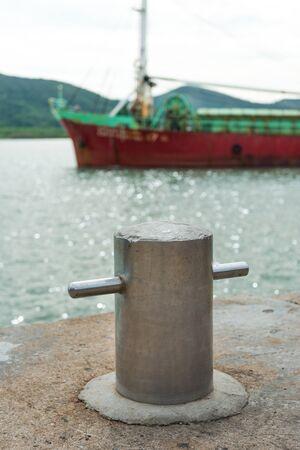 mooring bollard: Mooring Bollard with rope on pier by the sea