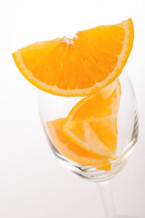 Fresh orange in glass on white background