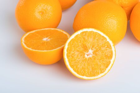 cleave: Fresh orange and cut in half on white background