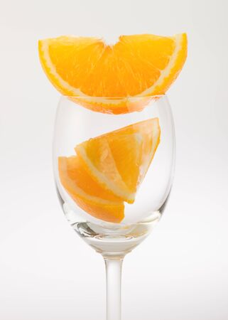 cleave: Fresh orange in glass on white background