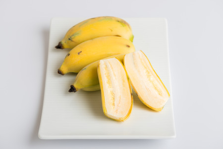Cultivated banana on a plate and white background. Reklamní fotografie