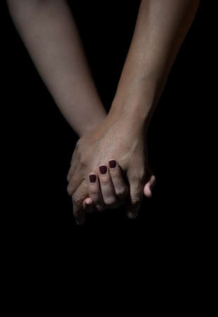participate: two hands of love people holding on a black background Stock Photo