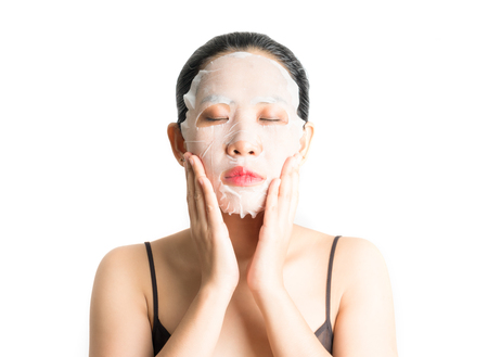 Young woman doing facial mask sheet with purifying mask on her face on white background