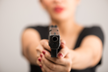 young woman asian girl holding a gun aiming at the gun, with selective focus 스톡 콘텐츠