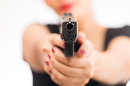 young woman asian girl holding a gun aiming at the gun, with selective focus Banque d'images