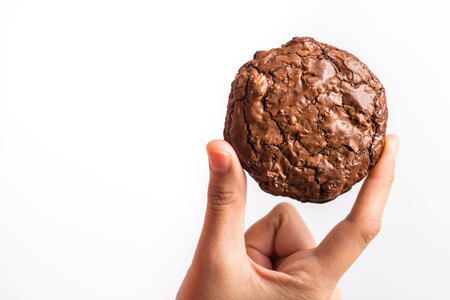 Close up hand holding sweet cookies chocolate brownie on white background, selective focus