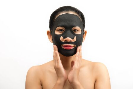 Young woman doing facial black mask sheet with purifying mask on her face on white background Stock Photo