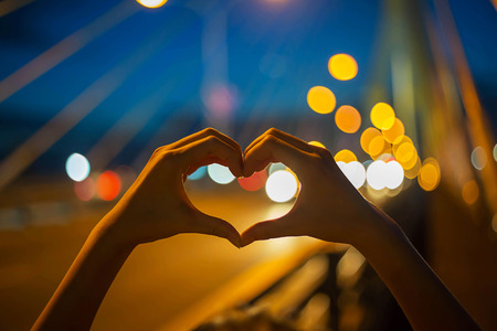 Love shape hand on bokeh backgound at twilight moment Stock Photo