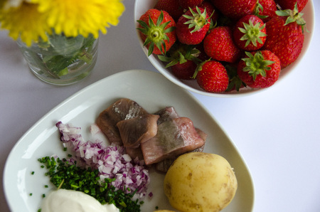 Pickled herring with new potatoes, chives, red onion and sourcream on a porcelain plate. A bowl of strawberries and midsummer flowers on the side.