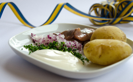 Pickled herring with new potatoes, chives, red onion and sourcream on a porcelain plate. Swedish holiday celebration. Traditional swedish food during midsummer.