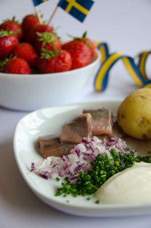 Pickled herring with new potatoes, chives, red onion and sourcream on a porcelain plate. A bowl of strawberries on the side. Stock Photo