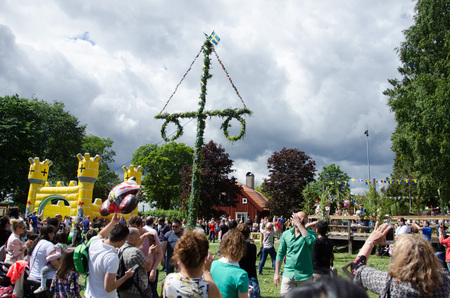 midsummer pole: Stockholm, Sweden - June 23 2017. People celebrating the swedish holiday midsummer by raising the maypole covered in flowers and leaves in Akalla, a suburb in northern Stockholm.