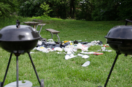 enviroment: Garbage left in the grass after barbecue and festivities has ended. Stock Photo