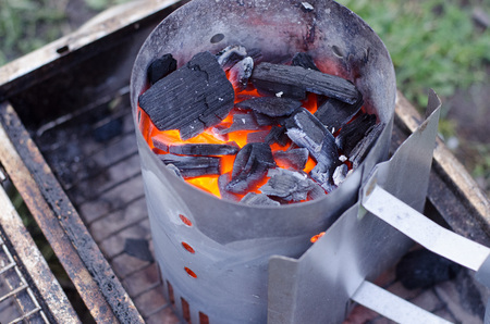 A chimney starter in use to get the charcoal ready for the grill in a more environmentally friendly way. Stock Photo