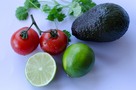 Avocado, lime cut in half, tomatoes on the vine and cilantrokoriander placed in a group on a white background