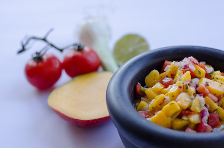 Mango salsa in a stone bowl with ingredients in the background