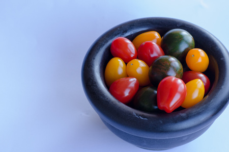 A variety of tomatoes in group in a bowl of stone on white background Stockfoto