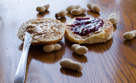 Peanut butter and jelly sandwich with whole peanuts spread on the table