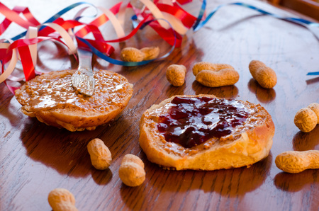 Peanut butter and jelly sandwich with whole peanuts spread on the table with red, white and blue bands in the background. Stockfoto