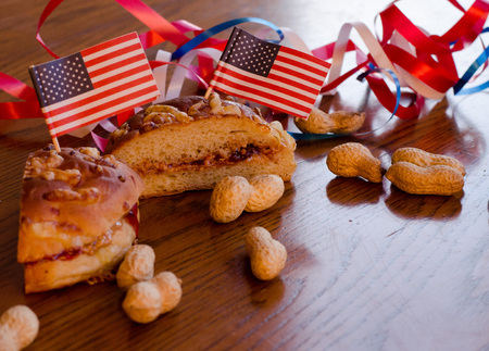 Peanut butter and jelly sandwich with american flags pinned to it and whole peanuts spread on the table with red, white and blue bands in the background.