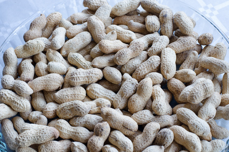 Peanuts in group on a tray of glass on table with silver cloth