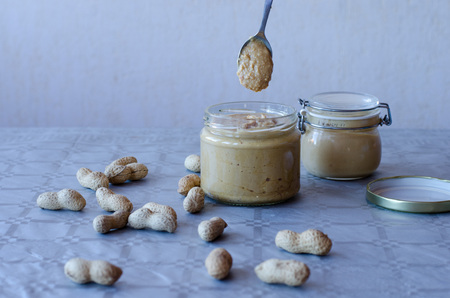 Homemade peanut butter in glass jar with peanuts spread on the table