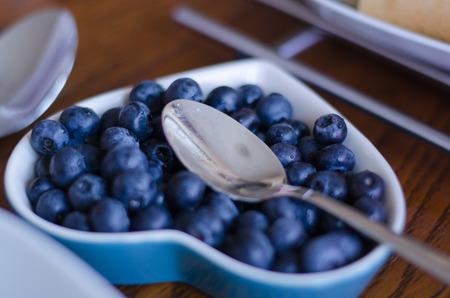 Fresh blueberries in group placed in a small bowl with a spoon in it.