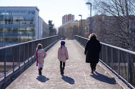 Family out for a walk over a bridge on a sunny day in urban scenery. Stockfoto - 120294500