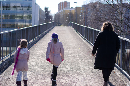 Family out for a walk over a bridge on a sunny day in urban scenery.