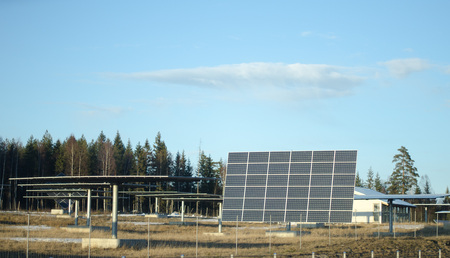 Solar panels in group on a field with a blue sky during early spring with some snow left on the grass.