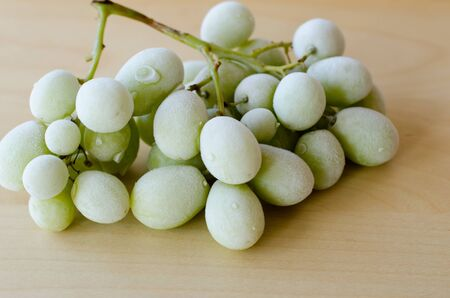 Frozen green grapes on a wooden table Stockfoto