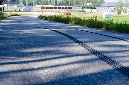 Skidmarks after a sudden braking on a narrow road with asphalt surface.