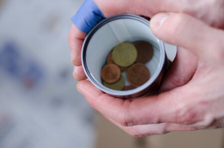 A person holding a cup with some coins begging for more change.