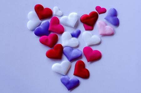Hearts in different colors and sizes on white background from above Stockfoto