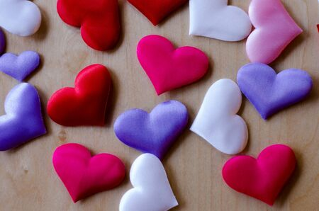 Hearts in different colors and sizes on wooden table