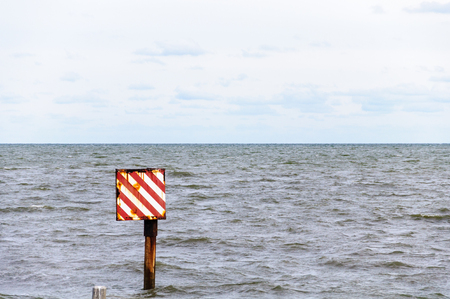 Red Stripe Waring Sign Stand In The Sea
