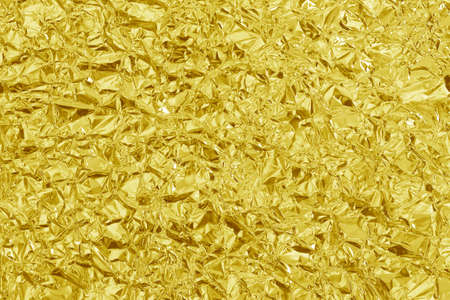 Shiny gold foil texture background, pattern of yellow wrapping paper with crumpled and wavy.