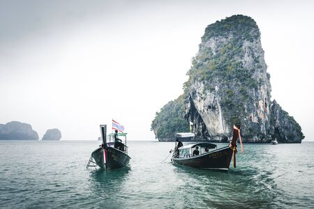 bad wheater conditions at tropical railay beach with longtail boats at Andaman Sea in Thailand