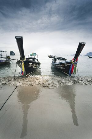 frontal shot of two longtail boats at railay beach in Thailand