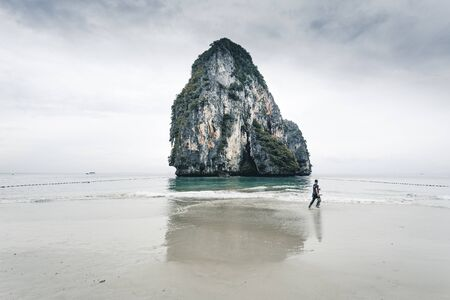 man running in front of big rock at railay beach in Krabi province, Thailand